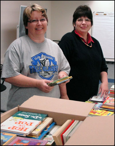 Two volunteers packing books
