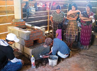 Guatemalan women watching workman building cook stove